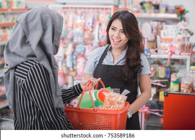 female cashier smiling to customer in supermarket