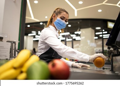 Female cashier in supermarket wearing hygienic protection mask and gloves while working risky job because of corona virus pandemic. Healthcare protection against covid-19.