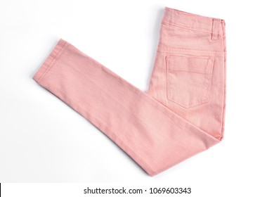 Female casual peach color jeans. Girls new middle waist trousers folded on white background. Female spring or summer skinny pants on sale.