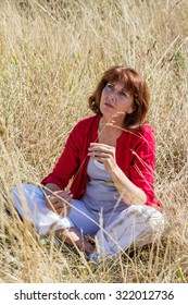 female casual relaxation - sad aging woman sitting in long dry summer grass seeking for solitude and peaceful silence from the city,summer daylight