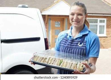 Female Caterer Delivering Tray Of Sandwiches To House