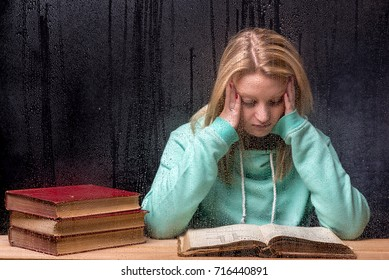 Female, Caucasian, blond wearing an aqua blue hooded sweater reading an  old book with other old books to one side,  behind a rain covered window, leaning on elbows hands either side of her face.