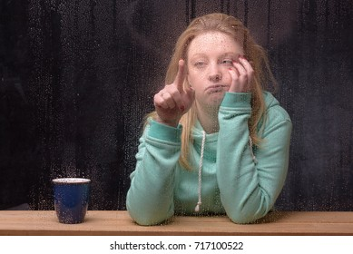 Female caucasian blonde twenties wearing a hooded sweatshirt drawing in the mist on a  a rain covered window  looking bored and lonely with nothing to do.