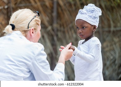 Female Caucasian doctor holding hands and talking with black African little girl outdoors in African village