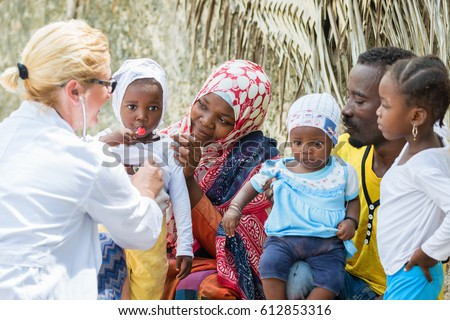 Female Caucasian doctor listening heart beat and breathing of little African girl with stethoscope, family looking medical exam