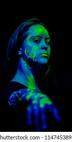 Female caucasian model with plant inspired green blacklight paint glowing. Shallow focus leaves the focus on the face
