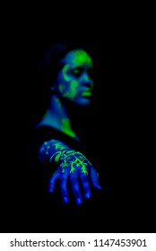 Female caucasian model with plant inspired green blacklight paint glowing. Shallow focus leaves the focus on the hand