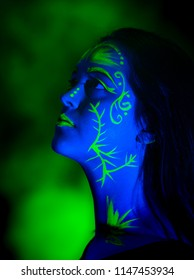 Female caucasian model with plant inspired green blacklight paint glowing. Brightly colored smoke flowing behind the model