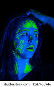 Female caucasian model with plant inspired green blacklight paint glowing.