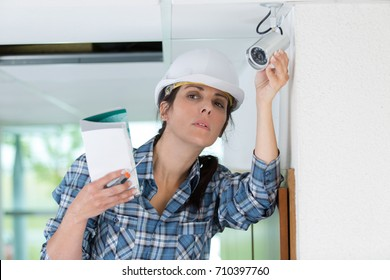 female cctv installer checking security camera
