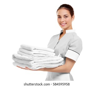 Female chambermaid  holding clean white folded towels on white background