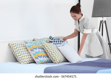 Female chambermaid making bed in hotel room