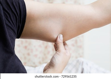 female checking her upper arm. Women with fat belly and big her arm, Lose weight and liposuction cellulite removal concept,