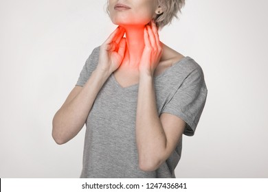 Female checking thyroid gland by herself. Close up of woman in white t- shirt touching neck with red spot. Thyroid disorder includes goiter, hyperthyroid, hypothyroid, tumor or cancer. Health care.