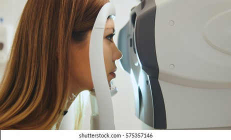 Female checks the eyes on the modern equipment in the medical center