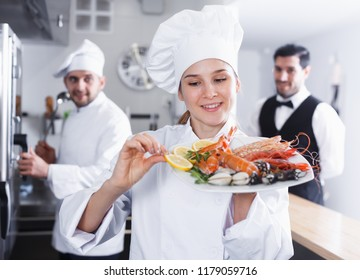 Female chef checking seafood dish in kitchen of restaurant before serving guests