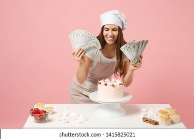 Female chef cook confectioner or baker in apron white t-shirt, toque chefs hat cooking cake cupcake at table hold money isolated on pink pastel background in studio. Mock up copy space food concept