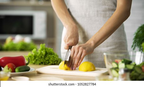 Female chef cutting lemon with sharp knife for lunch preparing, cooking tips