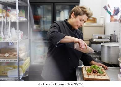 A female chef drizzling balsamic vinegar on an open sandwich
