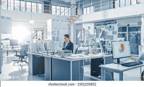 Female Chef Engineer Working on Computer, Programming Robot Arm in Bright Modern Industrial Robotics Technology and Design Office. Working in Research Facility.