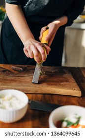 Female chef grating lemon zest on a wooden board