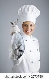 female chef holding up fresh fish