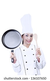 Female chef holding a pan and wooden spoon on white background
