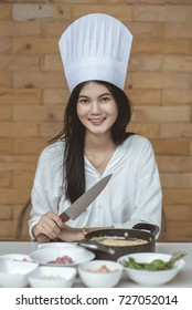 Female chef holding prepared dish in kitchen for cooking spaghetti Pad Kee Mao Seafood menu, Thai Food