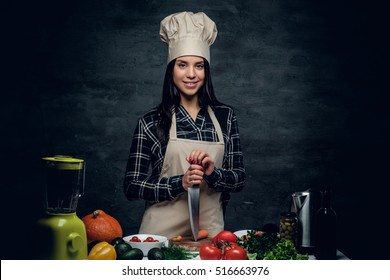 Female chef holds a knife and posing near a table with fresh vegetables.