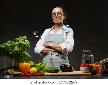 Female chef posing next to a table in kitchen. Studio photo on a dark background