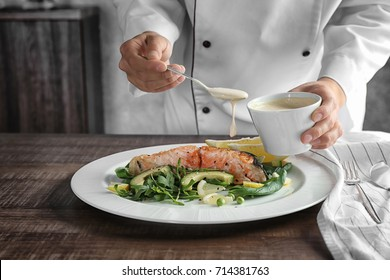Female chef pouring sauce onto plate with delicious salmon in kitchen