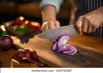 Female chef is precisely slicing red onions on a wooden cutting board in a restaurant.