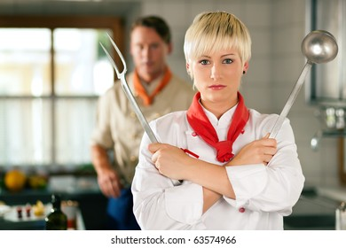 Female Chef in a restaurant or hotel kitchen posing with kitchen gear, in the background another chef