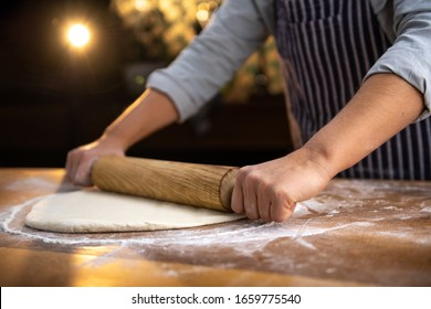 Female chef is rolling fresh dough with a dough roller on a wooden surface in a rustic style kitchen