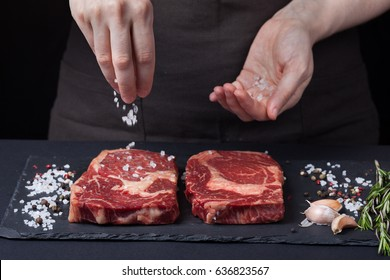 A female chef sprinkles sea salt with two fresh raw ribeye steaks from marbled beef on a dark background. Nearby is a mixture of peppers, garlic and rosemary.