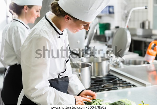 Female chefs at work in industrial kitchen of canteen