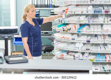 Female chemist arranging products in shelves at pharmacy