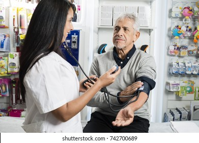 Female Chemist Checking Blood Pressure Of Senior Man