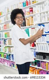 Female Chemist Holding Shampoo Bottle In Pharmacy
