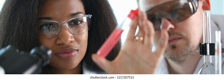 A female chemist holds test tube of glass in his hand overflows liquid solution potassium permanganate conducts an analysis reaction takes various versions reagents using chemical manufacturing.