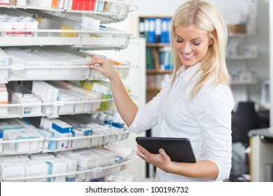 Female chemist standing in pharmacy drugstore with tablet PC