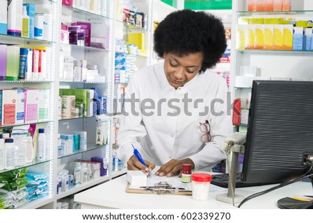 Female Chemist Writing On Clipboard At Counter