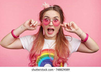 Female chick with pink hair tips, wears colorful clothes, has own specific style, ignores interlocutor, plugs ears with fingers, makes grimace, doesn`t want hear gossips. Female can`t stand loud sound