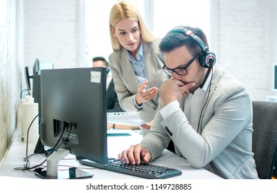 Female chief giving instruction to her worker. Problem in call center, male customer support worker doing bad his work.