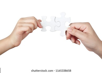 Female and child hand linking jigsaw puzzle pieces together isolated on white background