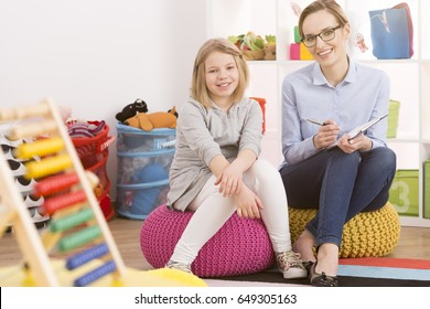 Female child psychologist and little girl sitting on poufs in classes