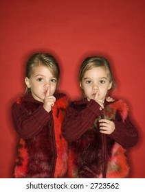 Female children Caucasian twins with fingers up to lips.