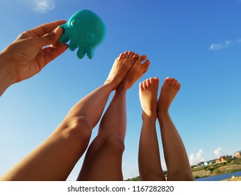 female and children's feet close up against the sky