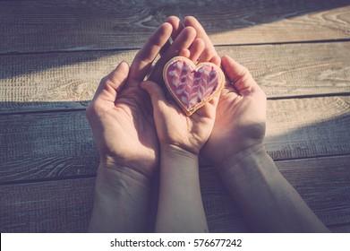 Weibliche und kinderreiche Hände halten Kekse in Herzform auf einem Holztisch. Sonnenlicht. Ein Konzept zum Muttertag. Vintage-Toning.