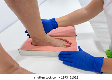 Female chiropodist, attending elder in a clinic and performing treatments podiatric, for the realization of insole for feet
